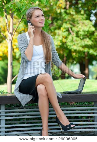 Young  business woman sitting on a park bench and talking on a cell phone outdoors