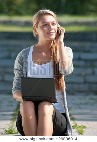 Young  business woman sitting on stairs and talking on a cell phone outdoors