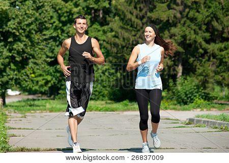 Pareja joven fitness de hombre y mujer a correr por el Parque