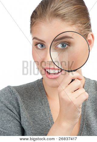 Pretty young woman looking through a magnifying glass. Isolated on white background