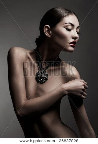 Fashion studio shot of beautiful naked woman with make-up and with a necklace around her neck