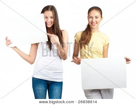 Two happy young women with blank signboards smiling and looking at camera, isolated on white background