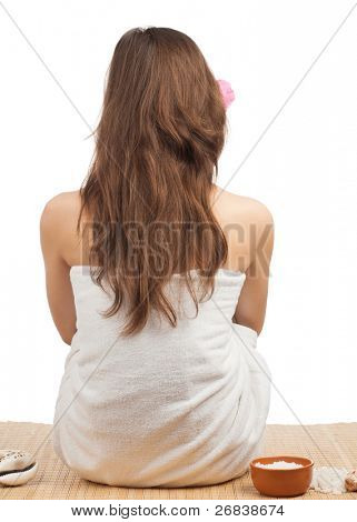 Rear view of young beautiful spa woman with long brown hair sitting at a spa salon