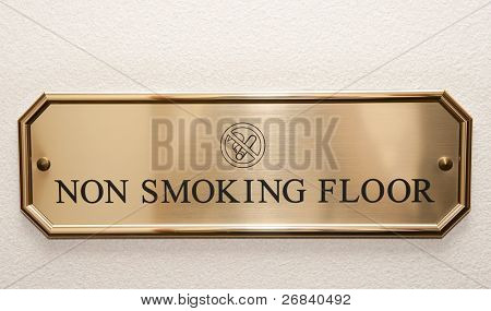 Shiny brass plate restricting smoking on hotel floor