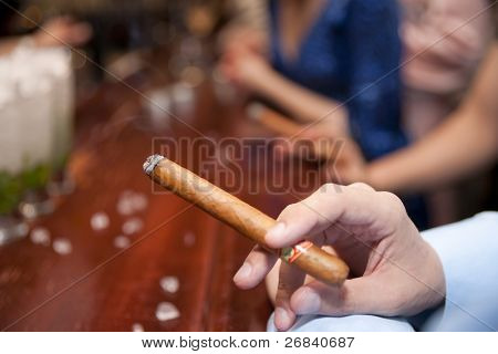 Man smoking cigar at bar counter, shallow focus