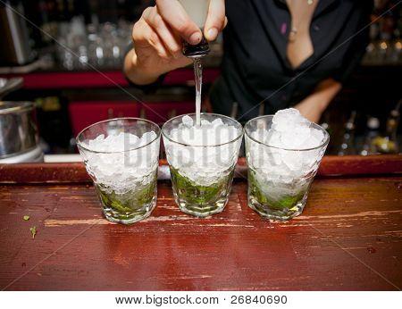 weibliche Barkeeper Gießen Saft in Glas Mojito vorbereiten.