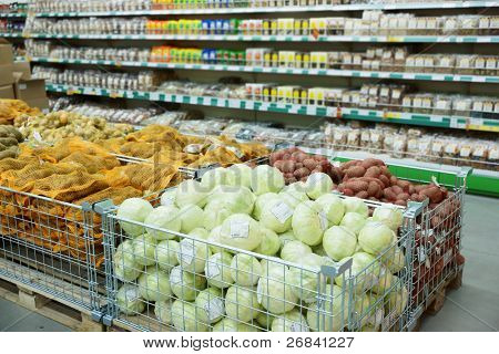 Vegetables and groceries in supermarket, focus is on cabbages