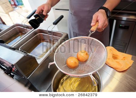 Chef cooking dim sum in a deep fryer - asian takeout food