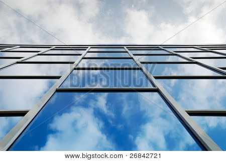Reflection of a cloudy sky in glass wall of an office building