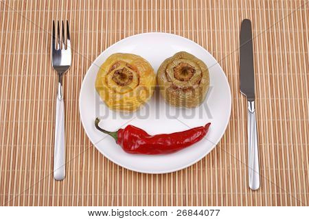 Stuffed paprika and red pepper smiling on a mat
