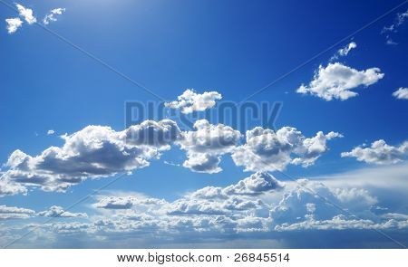Bright sunny clouds against midday blue sky