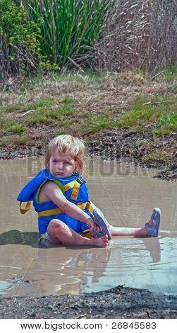 Toddler Girl Playing In Mud Puddle