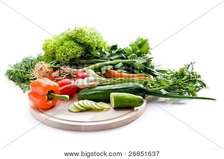 rohes Gemüse auf Schneidebrett auf weißem Hintergrund