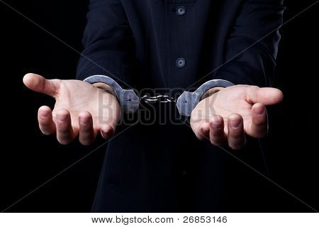 Business man in black suit and handcuffs