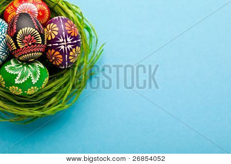 Painted easter eggs in basket on blue background
