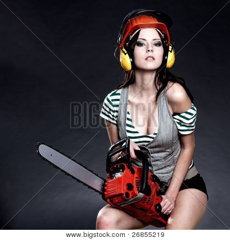 Studio photography of a girl with a chain saw on dark background