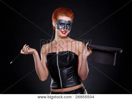 Mago mujer de hermosa pelirroja en oscuridad.