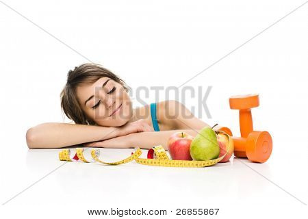 A studio shot of an attractive healthy young woman (personal trainer or exercise enthusiast) with fruits and a dumbbell.