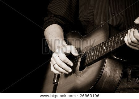 sepia image of man playing guitar