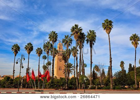 Tall Palms And Moroccan Flags Line Approach To Mosque And Minaret In Marrakesh.