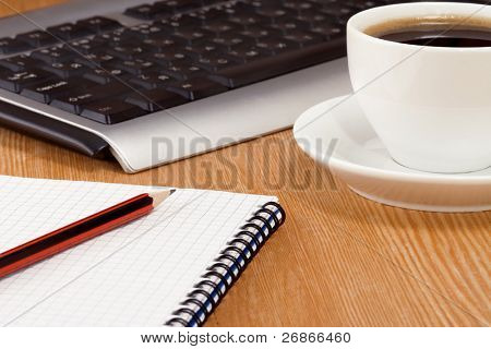 keyboard, notebook and cup of coffee on table