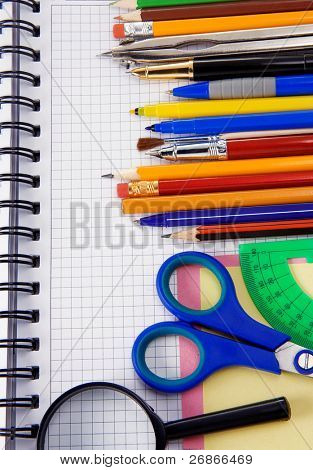 pens, pencils, magnifying glass and other office accessories on cheked notebook