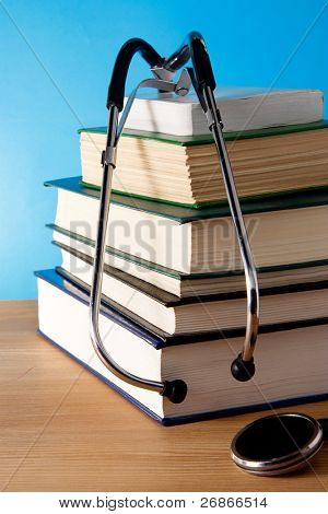 pile of book and stethoscope on blue background