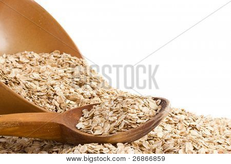oat flakes and wood spoon in ceramic plate isolated on white background