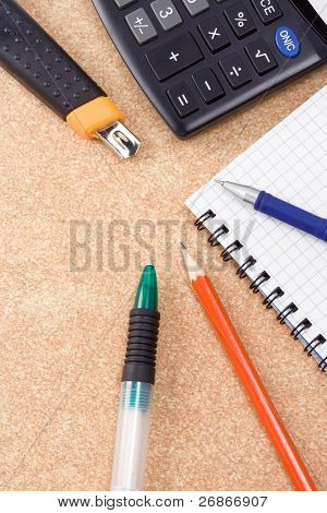 pen, pencil and paper knife with checked notebook on wood texture