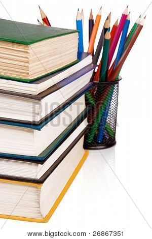 pile of old books and colorful pencils isolated on white background