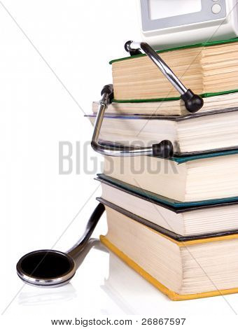 pile of old books and black stethoscope isolated on white background
