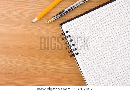 notebook and pens on wood table