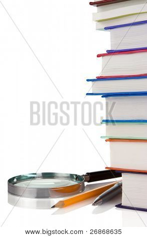 pile of new books, pen and magnifying glass isolated on white background