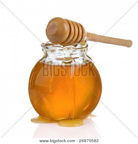 tarro de cristal lleno de miel y palo aislado sobre fondo blanco