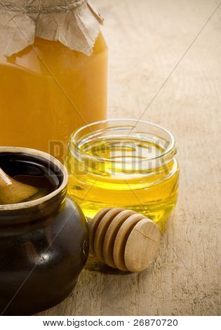 honey in jars and pot on wood table