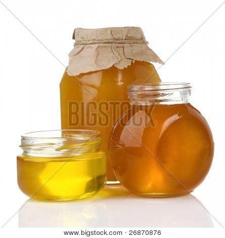 Topf mit Honig und Glas isoliert auf weißem Hintergrund