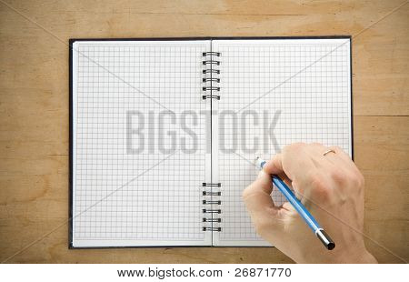 male hand writing by pencil on checked notebook