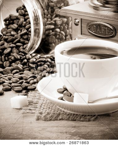 cup of coffee and grinder with roasted beans