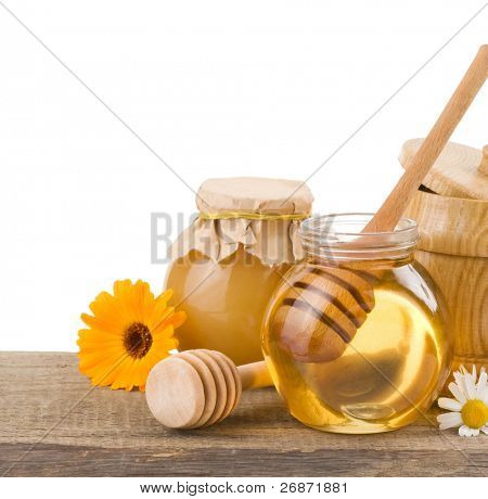 jar of honey and stick isolated on white background