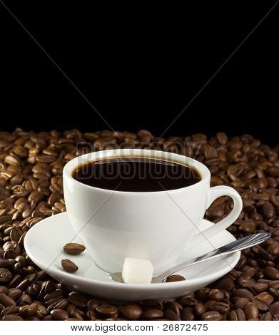 cup of coffee and sugar on beans isolated on black