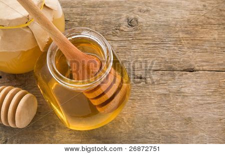 jar of honey and stick on wood background