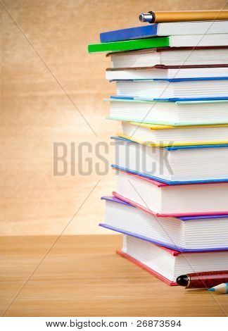 pile of books and pens on wood background texture