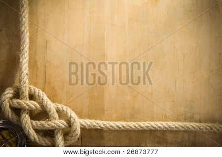 ship ropes and compass on old wood background