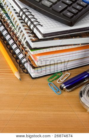 pile of notebook and pens on wood background texture