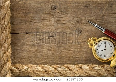ship ropes and watch with ink pen on old wooden background