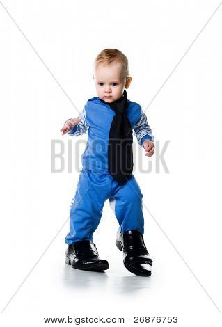 Little boy on the big shoes. Isolated on white