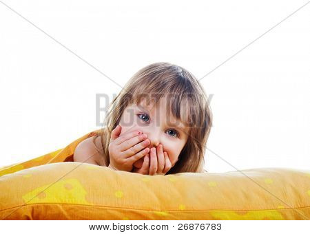 Little smiling girl on the bed. White background