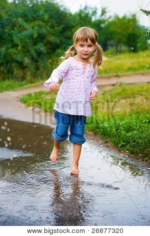 Girl junps barefoot in a puddle splashing water in the rain