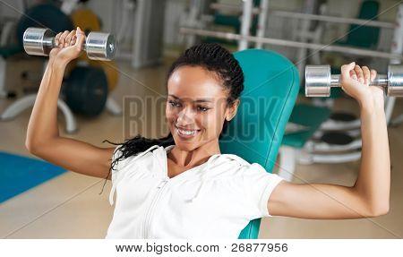 eine junge Frau freie Gewichte mit einem zuversichtlich Lächeln zu heben