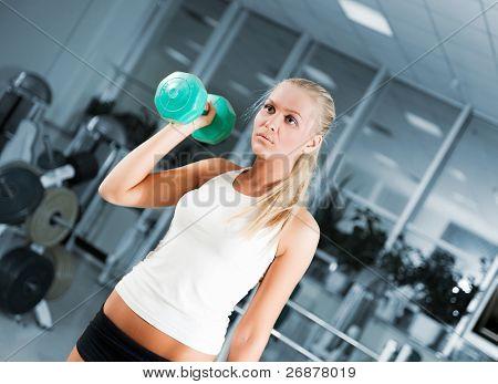 Eine junge Frau, das Heben von Gewichten mit einem zuversichtlich Lächeln